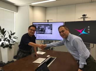握手を交わす町田氏と長谷川氏